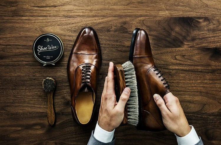 business man cleaning shoes