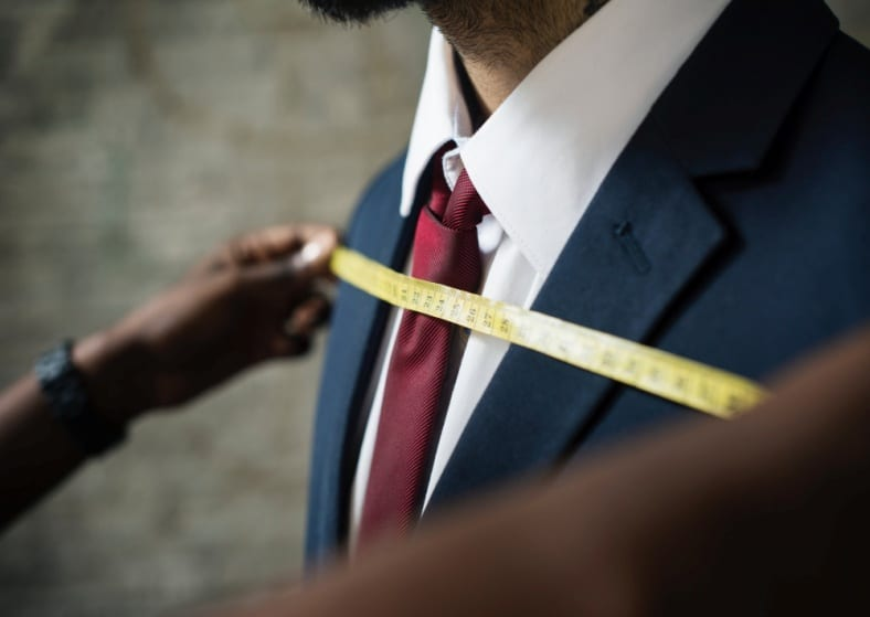a tailor taking measurements for a suit
