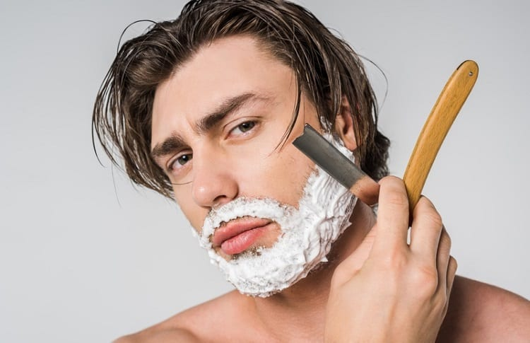 contrecrated man shaves with straight razor