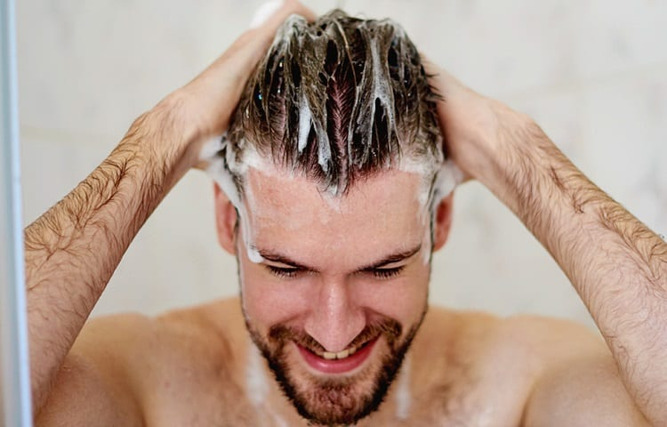 young man washes hair