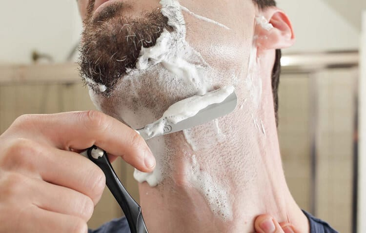 man shaves jaw and neck