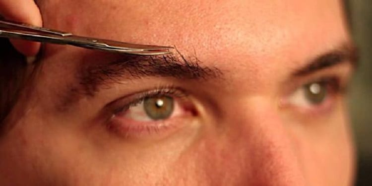 man trim eyebrows with small scissors