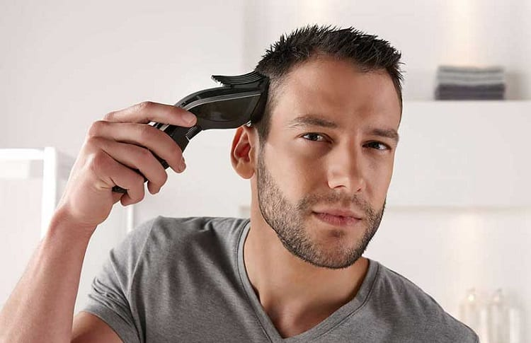 man cutting hair with clipper