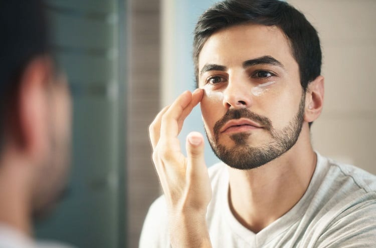 Man Applying Creme Under Eyes
